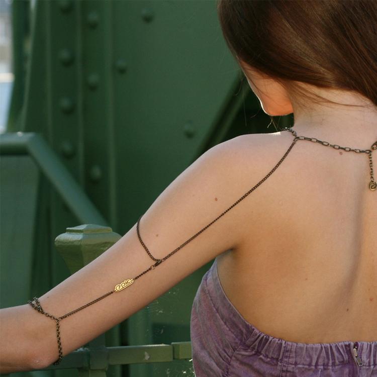 Koperkleurige boho ketting die van nek over de gehele arm loopt